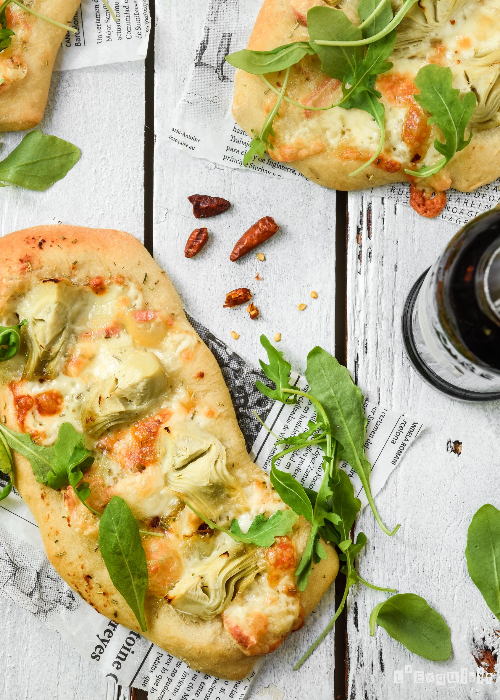 Pizza con queso, alcachofas y rúcula