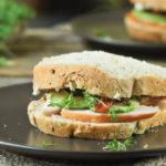Sandwich de pollo ahumado, aguacate y tomates en aceite