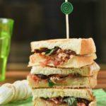 Sandwich mixto con tomates en aceite y albahaca